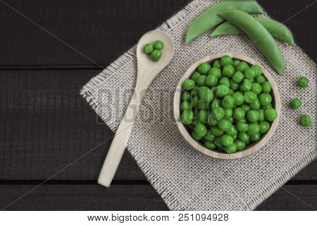 Wooden Bowl With Peas, Has Around A Wooden Spoon And Some Pods Of Peas, On A Wooden Board. In Horizo