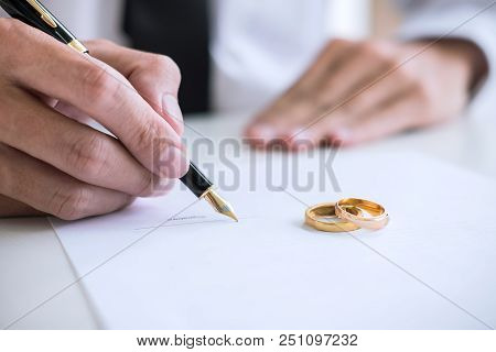 Hands Of Husband Signing Decree Of Divorce (dissolution Or Cancellation) Of Marriage Filing Divorce