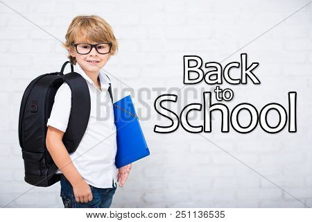 Portrait Of Little School Boy In Glasses With Backpack Over White Brick Wall