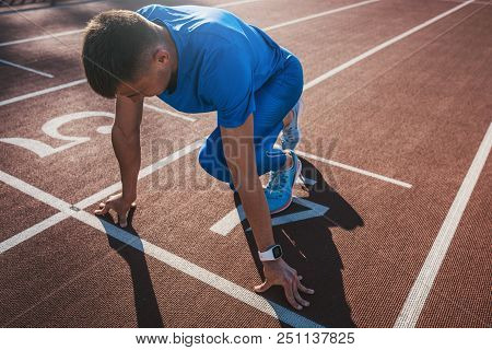 Side View Of Young Male Athlete At Starting Block On Running Track. Caucasian Sprinter Man In Starti