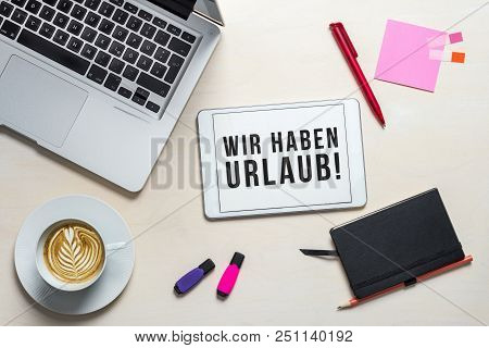 Wir Haben Urlaub Written In German On Tablet Meaning Closed For Holidays As Flatlay From Above Of An