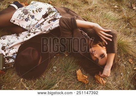 Autumn mood. Beautiful young woman lying on the autumn grass and yellow leaves. Seasonal autumn fashion.