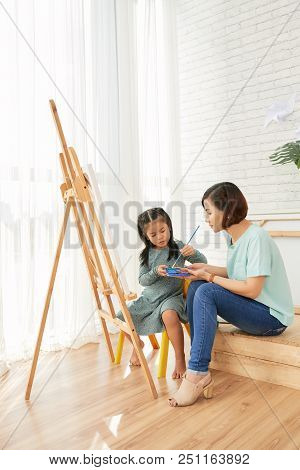 Side View Of Asian Teacher Woman And Student Girl Sitting And Drawing At Easel In Art Class