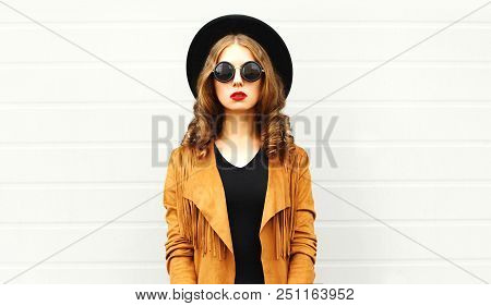 Elegant Woman Wearing A Retro Elegant Hat, Sunglasses, Brown Jacket And Black Handbag Clutch Over Gr