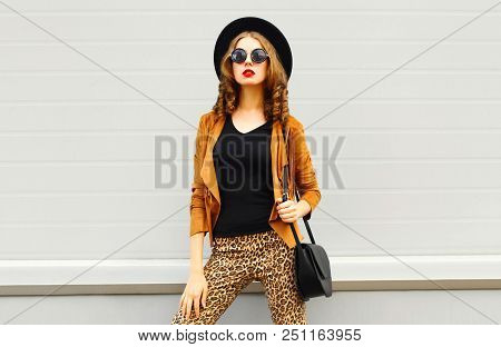 Beautiful Elegant Woman Wearing A Retro Elegant Hat, Sunglasses, Brown Jacket And Black Handbag Over