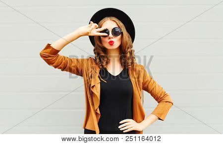 Cool Girl Wearing A Black Hat, Sunglasses And Jacket Having Fun Over Urban Grey Background