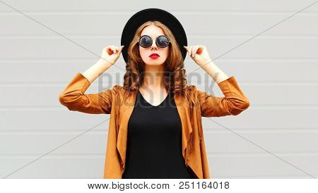 Elegant Pretty Woman Wearing A Black Hat, Sunglasses And Jacket Over Urban Grey Background