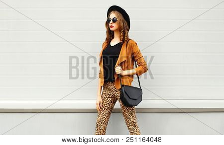 Beautiful Woman Wearing A Retro Elegant Hat, Sunglasses, Brown Jacket And Black Handbag Walking In C