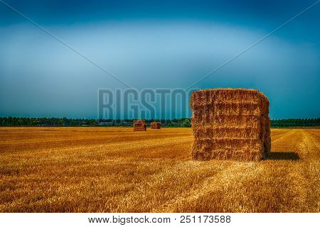 Dramatically Colored Image Of Rectangular Bales Of Straw Stacked On A Stubble Field After Harvesting