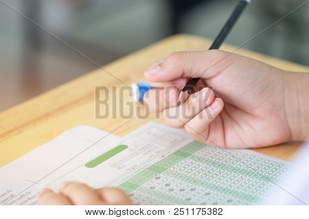 Student Taking Exams, Writing Examination On Paper Answer Sheet Optical Form Of Standardized Test On