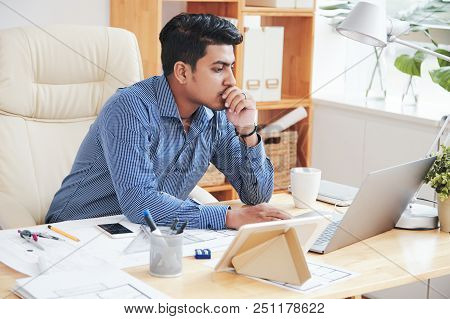 Adult Indian Employee Thinking And Using Laptop At Desk In Office