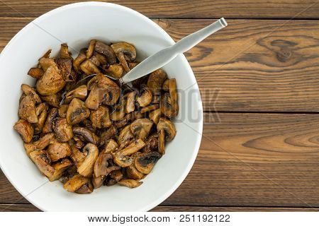 Overhead View Of Savory Cooked Mushroom Dish In Round White Bowl With Spoon Set On Wooden Table