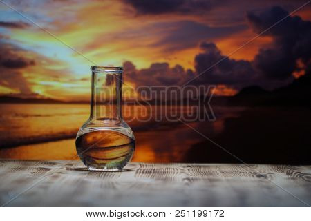 Clean water in a glass laboratory flask on wooden table on sunset background. Ecological concept, the protection of water resources, the test of purity and quality of water.