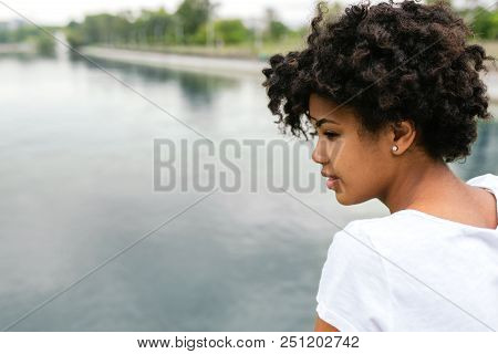 Side View Of Beautiful Happy Young Black Model With Short Curly Hairstyle Looking To The Lake In The