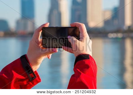 Female Hands Hold A Mobile Phone. Girl Is Taking Pictures Of San Diego Downtown On Her Mobile Phone.