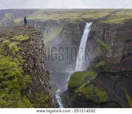 Valley Of River Fossa With Beautiful Haifoss Waterfall In South Iceland With Man In The Blue Jacket