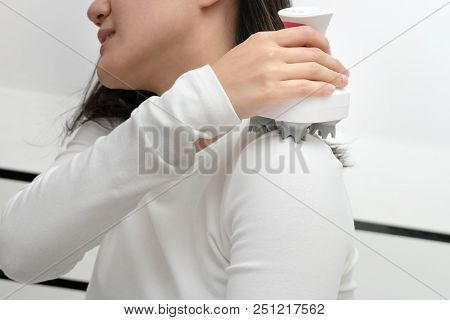 poster of electric arm, neck and shoulder massage machine on women shoulder, closeup, healthcare and medicine concept