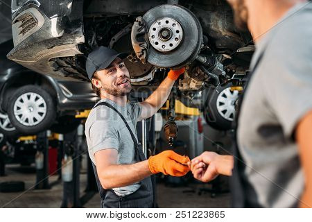 Professional Manual Workers Repairing Car Without Wheel In Mechanic Shop