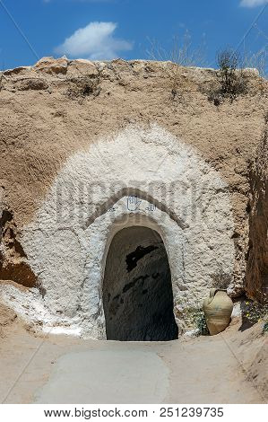 Tunisia, Matmata. The entrance to the cave dwelling of Berbers - troglodytes (in translation - living in caves). poster