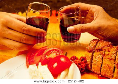 Romantic lunch setting for two with red wine fresh vegetables and bread