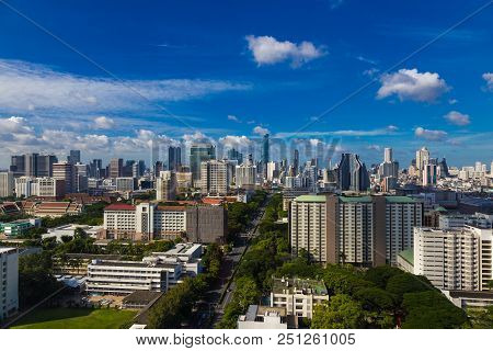 View of Bangkok skyline on a clear day, showing highrises against blue sky with white fluffy clouds poster