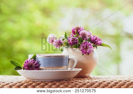Вeautiful Summer Composition Of A Cup Of Tea And Clover Flowers On A Natural Green Background, A Con