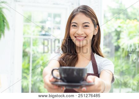 Asian Women Barista Smiling And Looking To Camera In Coffee Shop Counter. Barista Female Holding Cof