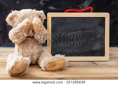 Teddy Bear Covering Eyes And A Blank Blackboard, Space For Text