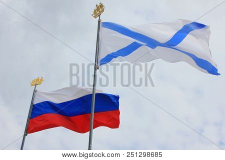 Russian Tricolor Flag and Russian Navy Ensign, also Known as St. Andrews Flag Isolated on Cloudy Sky Background. Naval Flag and National Flag of the Russian Federation. poster