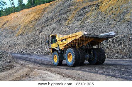 a panning shot a dump truck working on coal site