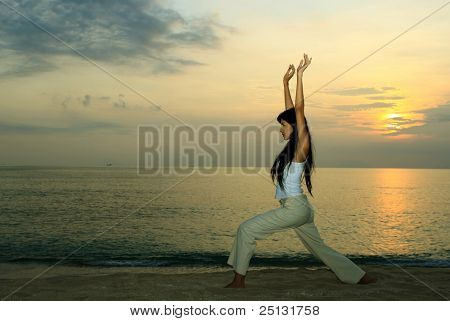 Young girl doing yoga exersice at sunset by the beach