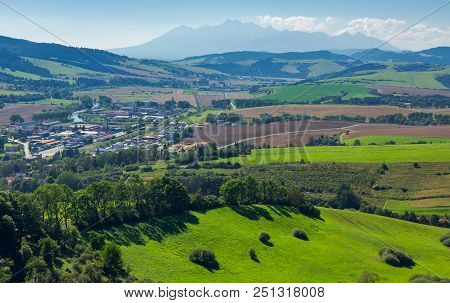 Rural Area Around The Town. Grassy Hill And Agricultural Fields. High Tatra Mountain Ridge In The Di