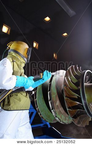 A worker sandblasting paint from a product