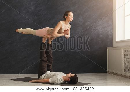 Young Couple Practicing Acroyoga On Mat In Gym Together. Woman Flying, Copy Space. Partner Yoga, Fle