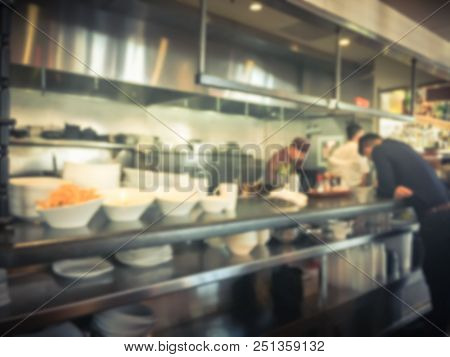 Blurred Background Chef Preparing For Lunch Service And Waiter Taking Ordered Dishes