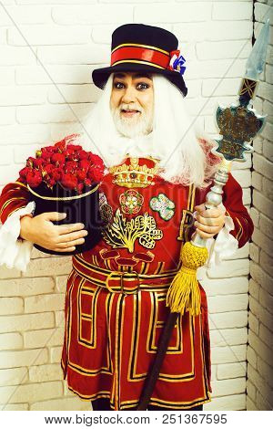 Amazed Senior Man Beefeater Yeomen Warder Or Male Royal Guard Bodyguard In Red Uniform With Flowers