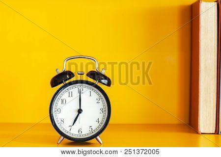 Alarm Clock And Book On Yellow Background With Copy Space.