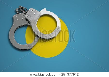 Palau flag  and police handcuffs. The concept of crime and offenses in the country. poster