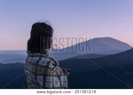 Girl Wrapped Up In A Blanket With A Cup Of Coffee And Disheveled Hair In The Pre-dawn Twilight In Th