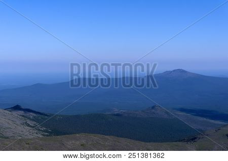 gently sloping mountains of the Northern Urals in a blue atmospheric haze poster