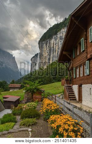Idyllic View Of Wooden Mountain Farm Houses In The Swiss Alps, Waterfall In The Background
