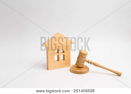Wooden House And Hammer Of The Judge On A White Background. Concept Trial Property. The Court Decisi