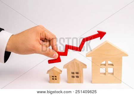 Businessman's Hand Holds The Red Arrow Up Above The Houses. The Concept Of Growth In Demand For Real