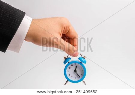 A Businessman's Hand Holds A Blue Alarm Clock On A White Background. The Concept Of The Flow Of Time