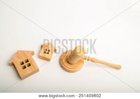 Two Wooden Houses And A Hammer Of The Judge On A White Background. The Concept Of Court Cases On Pro