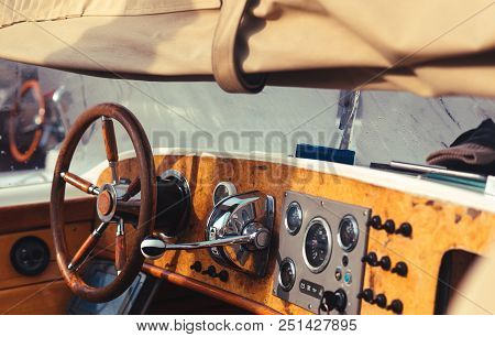Detail Of Vintage Wood Speed Boat With Bright Steering Wheel At Dock