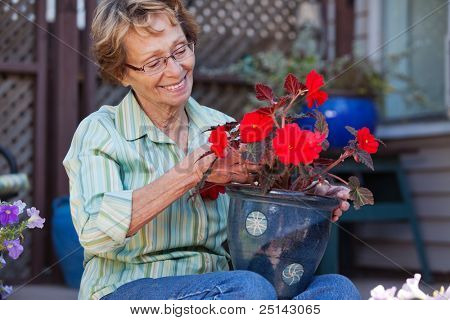 Cheerful senior woman looking at flower pot