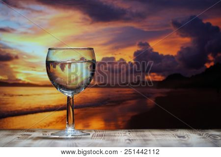A glass of drinking water is on a wooden table against the background of the sea sunset.