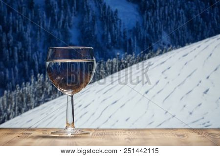 A glass of clean water stands on a wooden table against the winter mountain landscape.