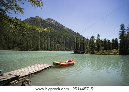Inflatable Red Boat In The Belterwiede Lake. Red Boat At The Wooden Bridge In The Blue Lake. Siberia